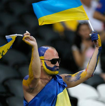 נקרא לדגל. אוהד אוקראיני מפגין תמיכה (צילום: EPA) (צילום: EPA)