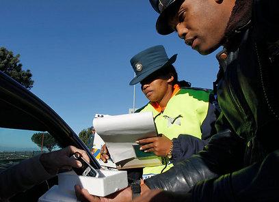 שוטרים מחרימים טלפון של נהגת, לאחר שהשתמשה בו בזמן הנהיגה בלי דיבורית (צילום: רויטרס) (צילום: רויטרס)