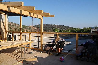 """""""ליצור אווירת לימודים נעימה"""". בניית הפרגולה בחצר (צילום: דורון הבסי)"""