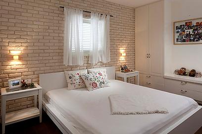 הקיר המגבה את המיטה מחופה בלבנים בהירות (צילום: שי אפשטיין) (צילום: שי אפשטיין)