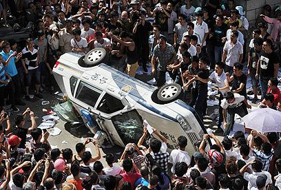 תושבים הופכים מכונית (צילום: AP, Kyodo News) (צילום: AP, Kyodo News)