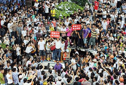 מפגינים בצ'ידונג. עוד הפגנה בשורה של הפגנות סביבתיות שהצליחו (צילום: AP, Kyodo News) (צילום: AP, Kyodo News)