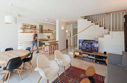 באזור הסלון שולב שטיח המתפקד ככתם צבע מושך בחלל, הנמצא בין ספה גדולה בצבע אפור ושני כיסאות לבנים (צילום: אביעד בר נס)