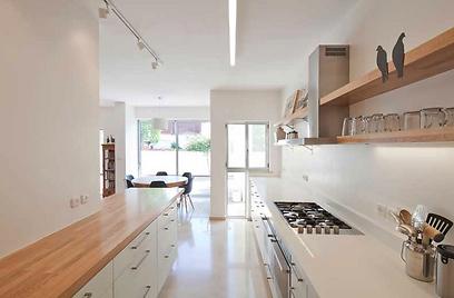 המטבח המוארך משלב ארונות לבנים ומשטח עבודה לבן יחד עם אי ישיבה מרכזי עם משטח עץ אלון טבעי (צילום: אביעד בר נס)
