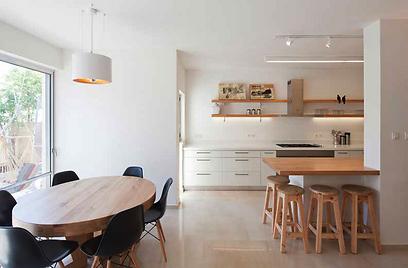 שולחן פינת האוכל העגול עשוי מעץ מלא הממשיך את הצבעוניות מאזור המטבח, מסביבו כיסאות מרופדים בבד שחור (צילום: אביעד בר נס)