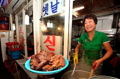 בעלת ביסטרו מכינה מרק כלב מסורתי (צילום: EPA) (צילום: EPA)