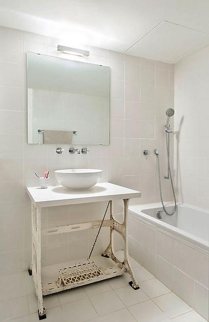 האמבטיה: מכונת תפירה ישנה שעברה במשפחה משמשת כמשטח לכיור בחדר האמבטיה של הבנות (צילום: בועז לביא ויונתן בלום)