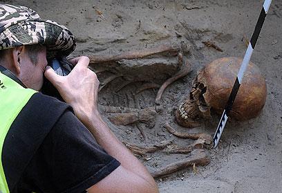 בסוף, נכנע לעינויי הקומוניסטים. ארכיאולוג מתעד את אחד השלדים (צילום: AP) (צילום: AP)