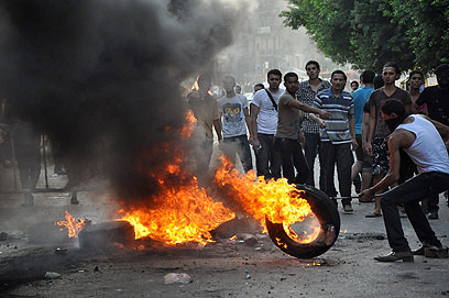 """שריפת צמיגים מול שגרירות ארה""""ב בקהיר, היום (צילום: AP) (צילום: AP)"""