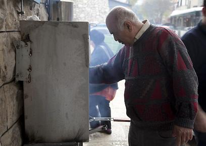 מלך הדגים של נצרת. גאזי הופך מוסרים על הגחלים (צילום: תום להט) (צילום: תום להט)