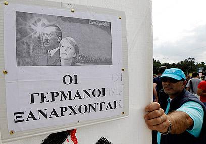 """""""הגרמנים באים"""". מרקל והיטלר על כרזה אחת באתונה (צילום: AP) (צילום: AP)"""