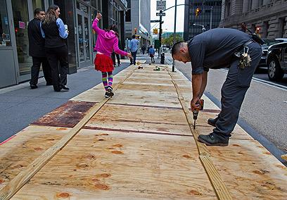 אוטמים את הפתחים במדרכה במנהטן (צילום: AP) (צילום: AP)