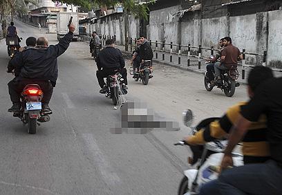 אחת הגופות נגררת ברחוב (צילום: רויטרס) (צילום: רויטרס)