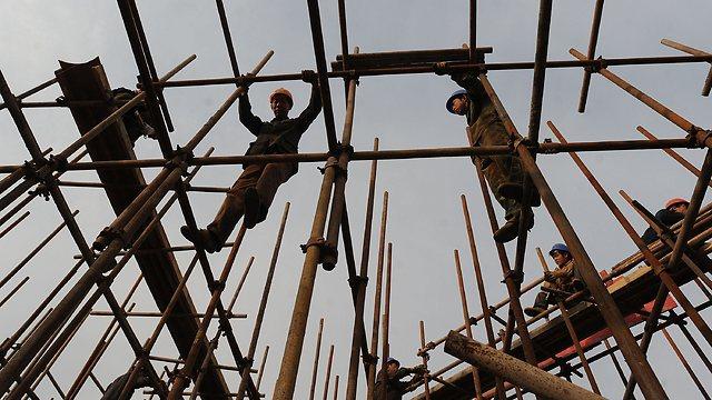 """פועלי בניין סינים. האינטרס הסיני הכלכלי בישראל הוא גדול, ובמיוחד בפרויקט המגלומני של קו הרכבת """"עוקף סואץ"""" מאילת לאשדוד (צילום: AFP) (צילום: AFP)"""