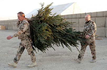 חיילי הקואליציה הבינלאומית נושאים עץ באפגניסטן (צילום: רויטרס) (צילום: רויטרס)