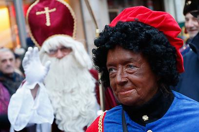 """מצעד לכבוד """"סינטרקלאס"""" בהולנד. ניקולאס הקדוש והעוזר """"זוורטה פיט"""" (צילום: רויטרס) (צילום: רויטרס)"""