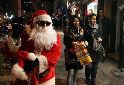 צעירות איראניות עוברות ליד אדם מחופש לסנטה קלאוס בטהרן (צילום: EPA) (צילום: EPA)