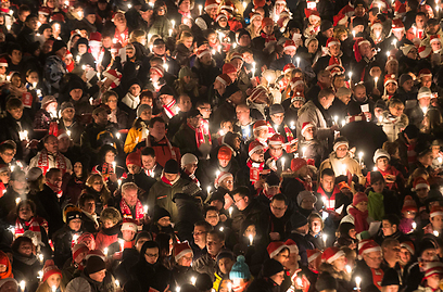 אוהדי קבוצת הכדורגל הגרמנית פ.צ אוניון מדליקים נרות בערב שירה שנתי לכבוד חג המולד (צילום: AP) (צילום: AP)