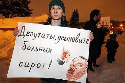 """הפגנה בסנט פטרבורג נגד החוק שאוסר אימוץ יתומים רוסים ע""""י אמריקנים (צילום: EPA) (צילום: EPA)"""