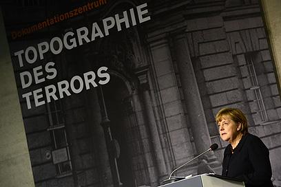 """מרקל בתערוכה. """"הדמוקרטיה לא יכולה להצליח לבדה"""" (צילום: AFP) (צילום: AFP)"""