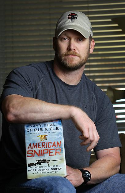 """כתב רב מכר על שירותו בעיראק. קייל עם ספרו """"צלף אמריקני"""" (צילום: AP) (צילום: AP)"""