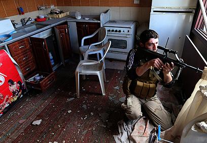 מורד צולף מחלון בית בפרבר של דמשק (צילום: רויטרס)