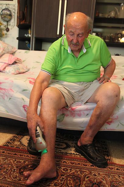 """יעקב לרנר ומכשיר הלייזר. """"תוך 3 חודשים לא היה זכר לפצע"""" (צילום: ליאורה אוסטרוף) (צילום: ליאורה אוסטרוף)"""