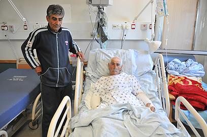"""""""לא תהיה יותר מאנרכיה"""". חוסני ברהוש ואביו בבית החולים (צילום: ירון ברנר) (צילום: ירון ברנר)"""
