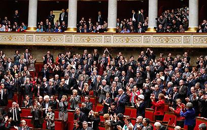 נציגי האסיפה מוחאים כפיים לאחר אישור החוק (צילום: EPA) (צילום: EPA)