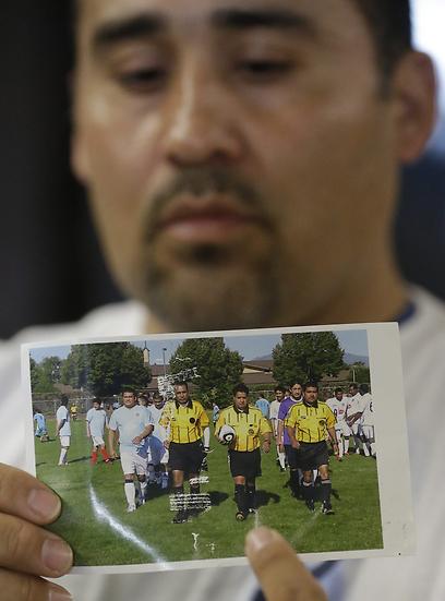 אחיינו של פורטיו מחזיק בתמונתו (צילום: AP) (צילום: AP)