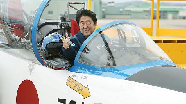 מדיניות החוץ של ממשלתו תהיה פעילה יותר? שינזו אבה במטוס קרב יפני (צילום: AFP)