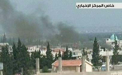 עשן מיתמר מעל העיר לאחר הפצצה (צילום: AFP,SYRIAN TV) (צילום: AFP,SYRIAN TV)
