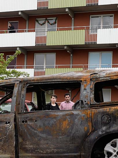 רכב שרוף בהוסבי. לפער החברתי הגדל במהירות הגדולה ביותר בקרב מדינות ה-OECD (צילום: AFP) (צילום: AFP)