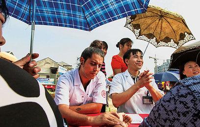 """שי שרעבי וד""""ר פאנג מטפלים במקומיים בשוק של זו'אנפנג  (צילום: רוני סופר) (צילום: באדיבות טבע הדברים) (צילום: באדיבות טבע הדברים)"""