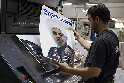"""כרזות בחירות של רוחאני. """"עצמאות, חירות, רפובליקה איראנית"""", (צילום: EPA)"""