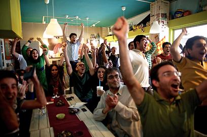 צעירים איראנים חוגגים בבית קפה את עליית נבחרתם לטורניר גביע העולם בכדורגל אחרי שגברו על דרום קוריאה בתוצאה 0:1 (צילום: AFP) (צילום: AFP)