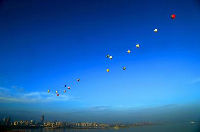 15 כדורים פורחים עוברים מעל מצר קיאונגזו בדרום סין במסגרת תחרות שבה הם צריכים לחצות את המצר תוך שעתיים וחצי (צילום: AFP) (צילום: AFP)