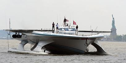 הספינה הסולארית הגדולה ביותר בעולם, MS Turanor PlanetSolar משווייץ, עוברת ליד פסל החירות בדרכה לעיר ניו יורק. על סיפון הספינה מדענים מז'נבה שחוקרים שינויי אקלים במי המפרץ (צילום: AFP) (צילום: AFP)