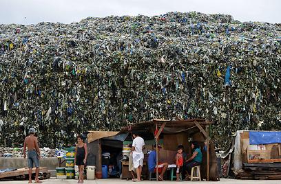 תושבים עומדים ליד אתר פסולת בבירת הפיליפינים מנילה. העירייה אסרה על שימוש בשקיות פלסטיק וקופסאות אוכל מקלקר כחלק ממאמציה להקטין את כמות הפסולת שמיוצרת על ידי התושבים (צילום: AFP) (צילום: AFP)