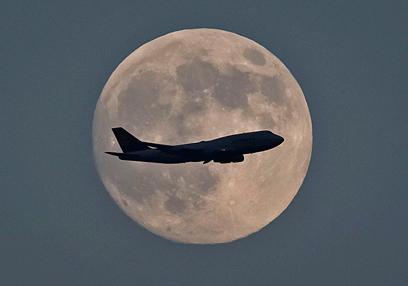המטוס לא מצליח להסתיר את הירח מעל שדה התעופה בפרנקפורט (צילום: EPA) (צילום: EPA)