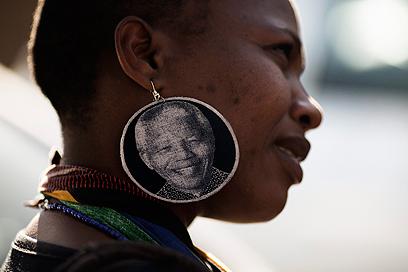 תושבת דרום אפריקה מחוץ לבית החולים שבו מאושפז מנדלה בפרטוריה (צילום AFP) (צילום AFP)