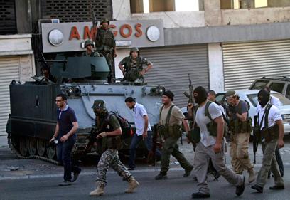 תומכיו של השייח אחמד אל-אסיר צועדים ברחוב בצידון ליד כוח צבא (צילום: AP)