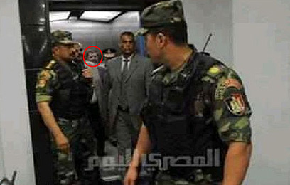 Morsi escorted by military officials