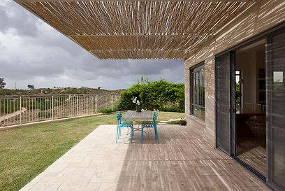 פרגולה מברזל ובמבוק. הקירוי מאפשר זרימה של אוויר ויוצר משחקים של אור וצל (צילום: עמית גירון) (צילום: עמית גירון)
