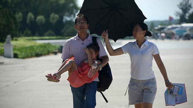 מחזה נדיר בסין. הורים ובתם בבייג'ינג (צילום: AFP) (צילום: AFP)