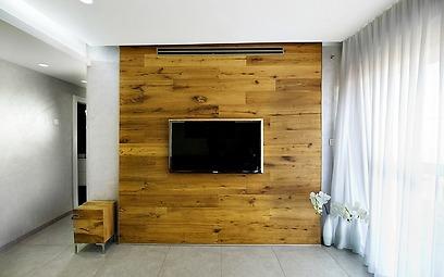 קיר הטלוויזיה חופה בעץ אלון מבוקע והקיר החזיתי כוסה בווילון נשפך במראה עדין (צילום: אופיר הראל) (צילום: אופיר הראל)