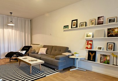 לצד הספה נתלו מדפים לבנים צרים עבור התמונות השונות של בעל הדירה (צילום: אלכסנדרו סורל) (צילום: אלכסנדרו סורל)