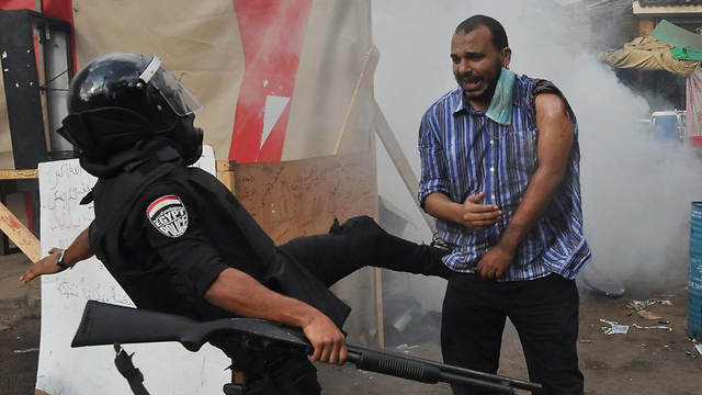 שוטר בועט באיש האחים המוסלמים (צילום: AP) (צילום: AP)
