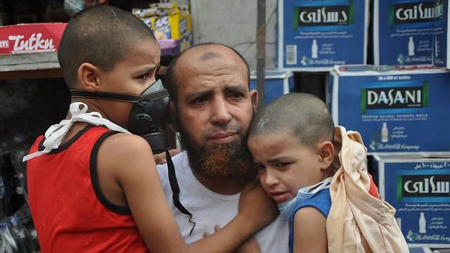 מפגין וילדיו לאחר פינוי אחד המתחמים (צילום: AP) (צילום: AP)
