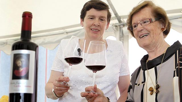 """חימנז ובקבוק יין שנושא את הציור. """"עכשיו נראה שכולם שמחים"""" (צילום: EPA)"""